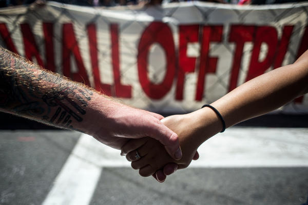 Protesters link hands during a demonstration against Republican presidential nominee Donald Trump in front of the Quicken Loans Arena on Wednesday.