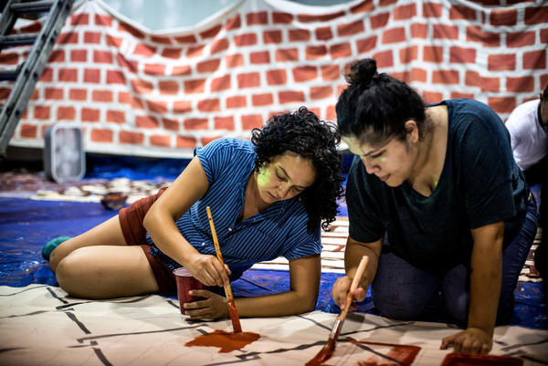 """Marisa Franco (left), an organizer with Mijente, and another volunteer paint a portion of """"wall"""" for the protest."""