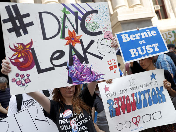 Demonstrators held signs outside the Democratic National Convention on Monday in Philadelphia. On Sunday, Debbie Wasserman Schultz, announced she would step down as DNC chairwoman at the end of the party's convention, after thousands of internal DNC emails were posted by the website Wikileaks.