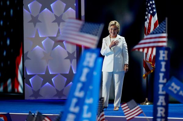 Democratic presidential candidate Hillary Clinton takes the stage in a snowy white pantsuit.