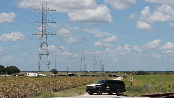 Authorities investigate the site of a hot air balloon accident in Maxwell, Texas, on Saturday. All 16 people aboard the hot air balloon died after it hit tall, high-voltage power lines.