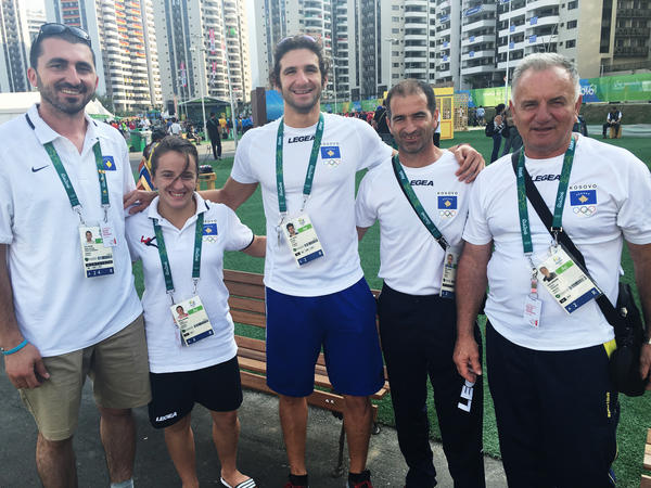 Swimmer Lum Zhaveli (center) stands with members of his team from Kosovo.