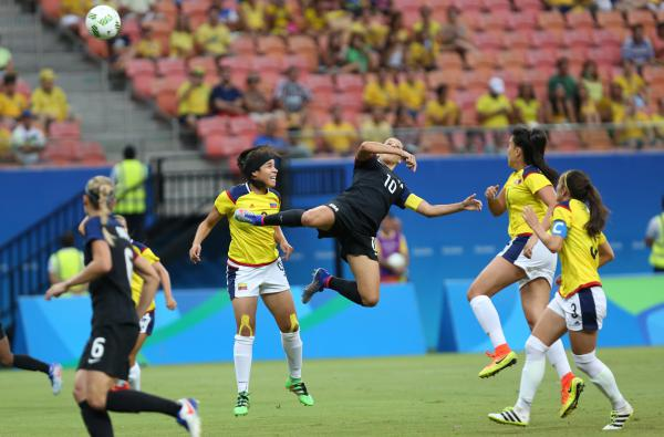 Carli Lloyd of the U.S. (center) jumps for a header during a match with Colombia on Tuesday that ended in a 2-2 draw. The U.S., which won its two previous matches, advanced from its group to the quarterfinals on Friday.