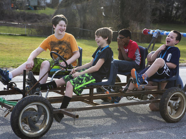 Sean Davis (left), Stephen Geisler, Rithik Kavanakudy and Andy Patterson laugh as they test drive the cart that will power their kinetic sculpture. Each year they reuse the cart's frame, which includes classroom chairs and bike chains, and create a new sculpture to go on top.