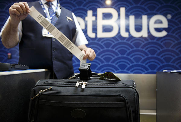 A JetBlue Airways Corp. employee tags a traveler's bag at the ticket counter inside Long Beach Airport in Long Beach, Calif.