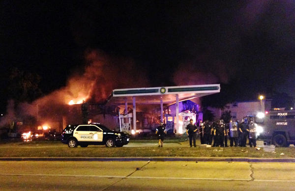 A crowd of protesters skirmished with police Saturday night in the Milwaukee neighborhood where an officer shot and killed a man after a traffic stop and foot chase earlier in the day, setting fire to a police car and torching a gas station.