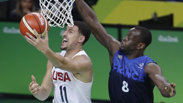 United States' Klay Thompson avoids France's Charles Kahudi for a layup Sunday. The U.S. won their third straight close game, 100-97, as Thompson led the way with 30 points.