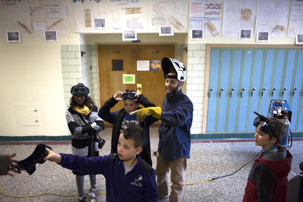 Mr. Guarraia and students wear protective gear before welding part of the sculpture's frame in a hallway at Arbutus Middle School.