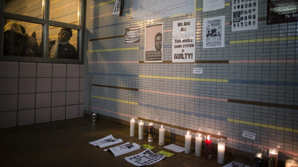 A demonstrator peers at a memorial to Akai Gurley at a public housing complex in Brooklyn, N.Y. Gurley was shot and killed by an NYPD officer in November 2014.