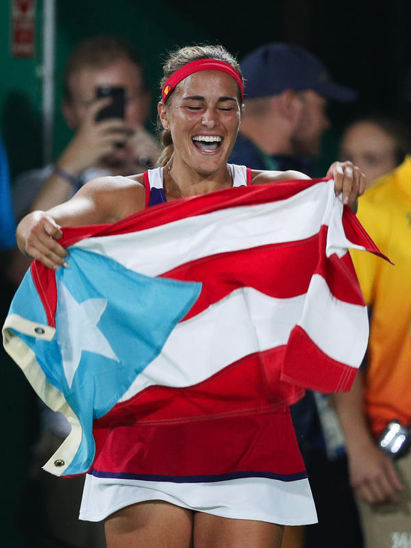Monica Puig of Puerto Rico celebrates holding her country's flag after winning the gold medal match in the women's tennis competition — Puerto Rico's first-ever Olympic gold medal.