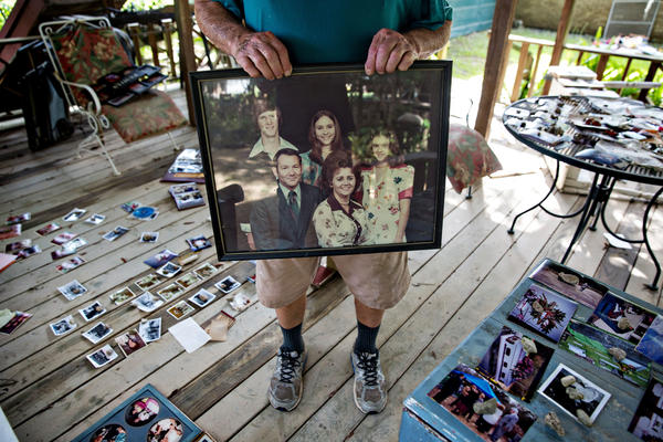 Hilton Pray, 82, holds one of thousands of his photographs that were damaged after an estimated 4-feet of water filled his home in Denham Springs, La.