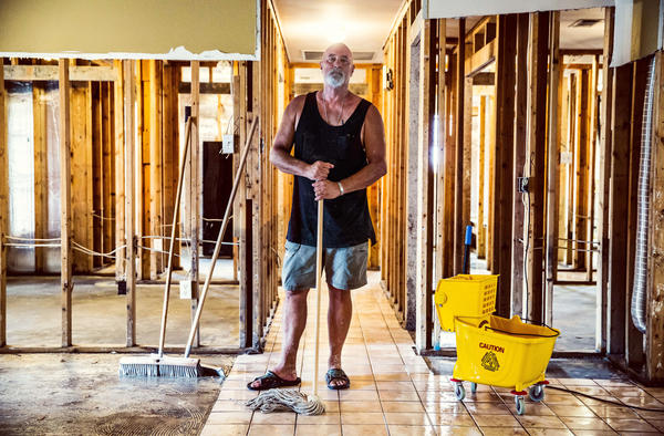 """Phillip """"Mooney"""" Brignac, 58, works on cleaning up his home, where he's lived since 1991, raising two children during that time. """"We will definitely rebuild. We are St. Amant strong. We will do whatever we've got to do,"""" he said."""