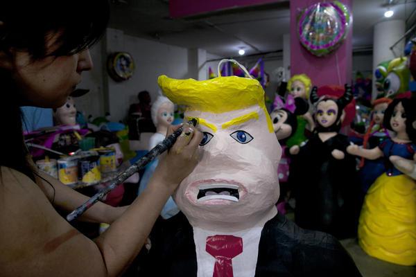 Alicia Lopez Fernandez paints a piñata depicting Donald Trump at her family's store, Piñatas Mena Banbolinos, in Mexico City in 2015.