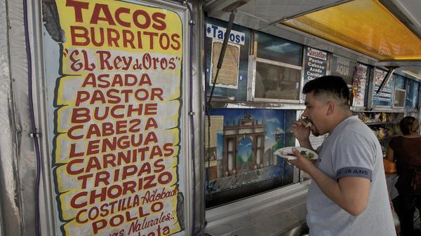 """Alejandro Flores eats a taco at """"El Rey de Oros"""" taco truck in the Whittier district of east Los Angeles."""