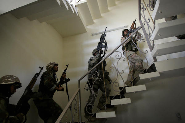 U.S. soldiers and Iraqi national police race up a staircase as they search a house in Baghdad in 2007. The U.S. surge in Iraq drove back Islamist radicals at that time. The gains were lost after the U.S. withdrew from Iraq in 2011, but the Americans have returned with an air campaign against the Islamic State.