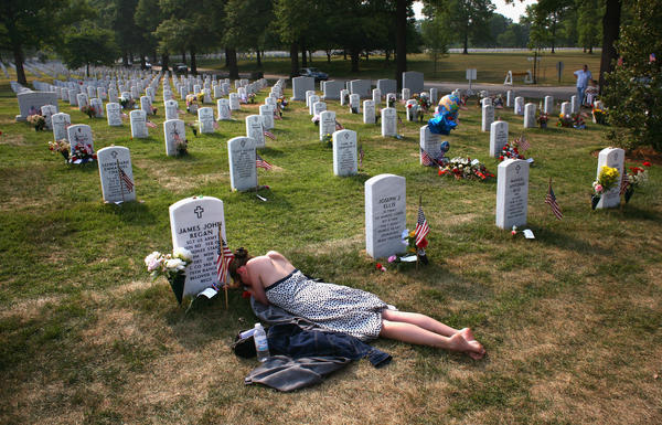 Mary McHugh mourns her slain fiance, Sgt. James Regan, at Arlington National Cemetery in 2007. Regan, a U.S. Army Ranger, was killed by a bomb in Iraq earlier that year. Nearly 7,000 U.S. military personnel have been killed and more than 50,000 wounded in the past 15 years of war.