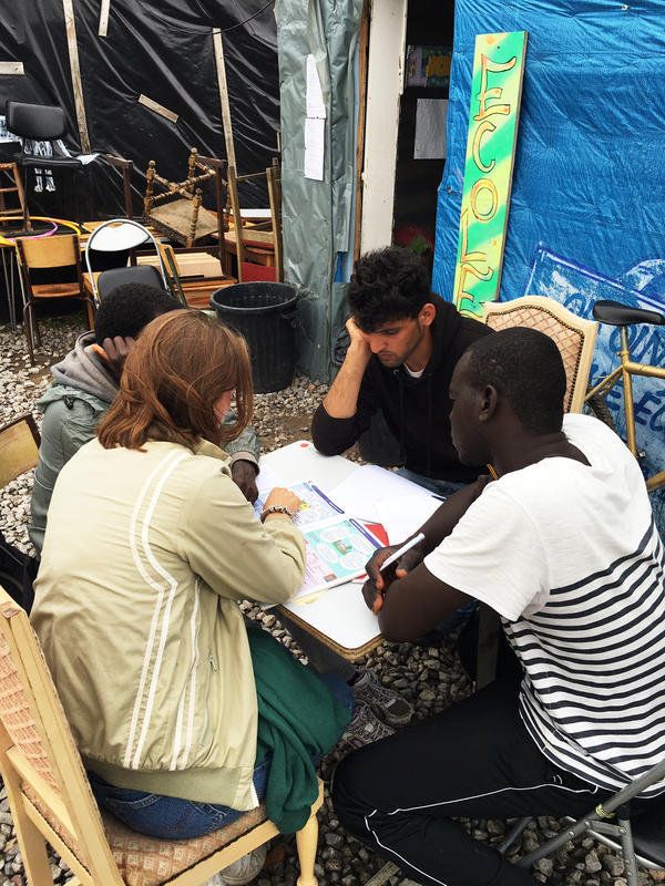 A volunteer at The Jungle gives migrants an English lesson there.