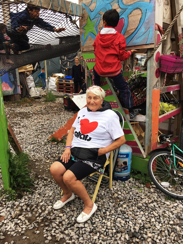 "Wearing an ""I Heart Calais"" T-shirt, Nicole Cordier visits a part of The Jungle where children can play. Some at the camp ask how she got a small cut on her knee. ""No one in Calais ever asked me about that,"" she says."