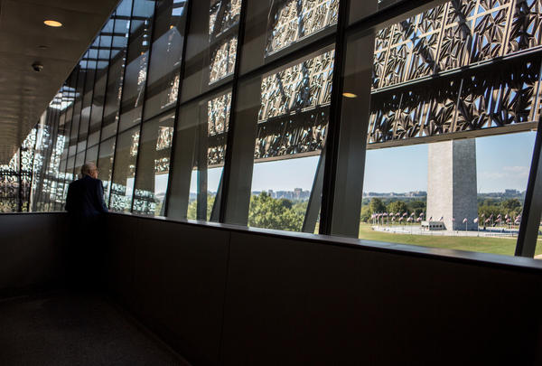 A visitor takes in a view of the National Mall through the panorama window at the NMAAHC.