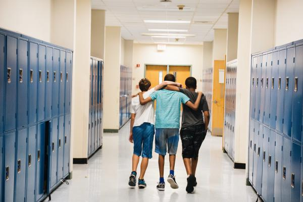 Bryan Bailey (right) and friends walk down the hallway arm in arm.