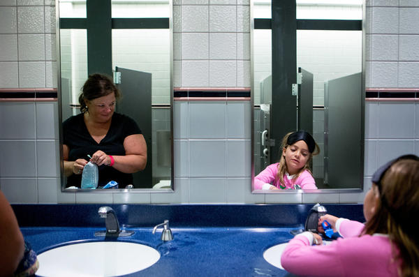 Pam Cross (left) watches her daughter, Healey, 8, as they brush their teeth in the museum bathroom before bedtime.