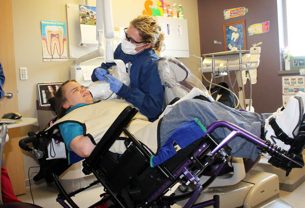 Beth Rown (right), a dental hygenist who cares for patients with special needs, cleans Lindsay Klecker's teeth.