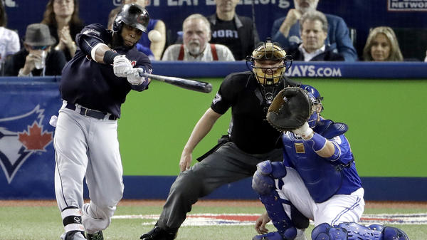 Cleveland's Carlos Santana hits a home run in the Indians' 3-0 win over the Toronto Blue Jays in Game 5 of the ALCS on Wednesday. With the victory, the Indians advance to the World Series for the first time since 1997.