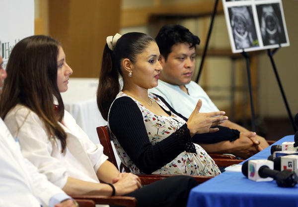 Yessica Flores (center), who became infected with the Zika virus early in her pregnancy this summer, told Miami reporters this week about her worries. The fetus looks healthy so far, doctors say. Flores and her husband, Selvin Yac (right), will name the baby Daniela Elizabeth.