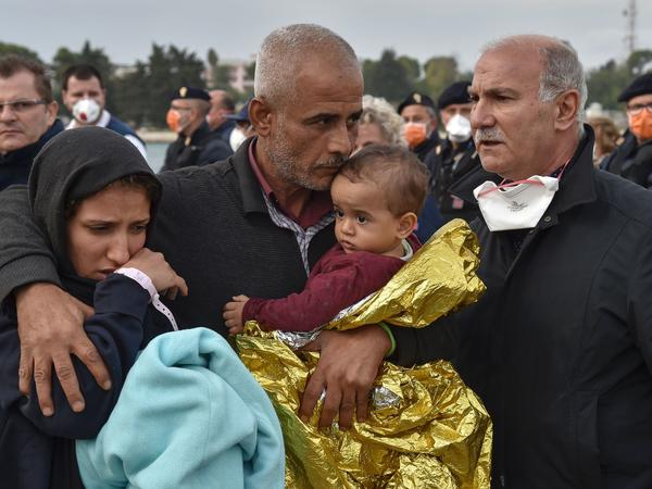 A family disembarks from the Topaz Responder, a rescue ship, Oct. 27 at Brindisi in southern Italy. The ship arrived with 347 migrants and refugees from Central Africa and Syria following a rescue operation off the Libyan coast.
