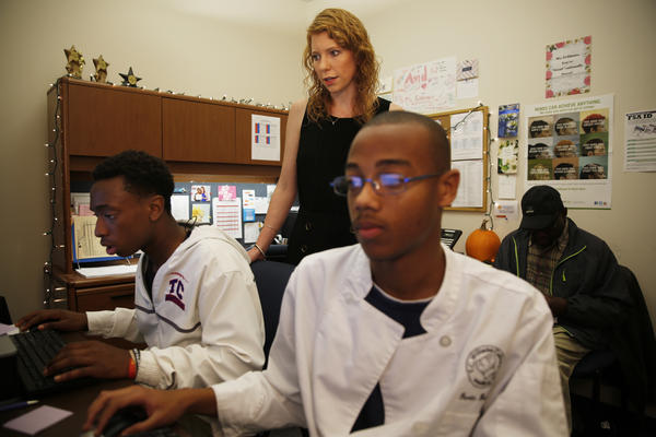 Margaret Feldman helps students (from left) Al Nagib Conteh, 17, and Devin Butler, 18, as they work through their FAFSA applications. Conteh's father, Ahmed Conteh (back), is there to help his son through some of the harder questions.