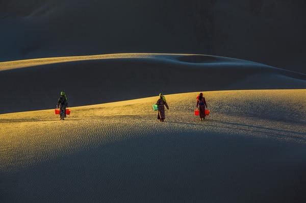 As the sun rises over the Naiman Desert in Inner Mongolia, China, girls carry buckets on their way to get water.