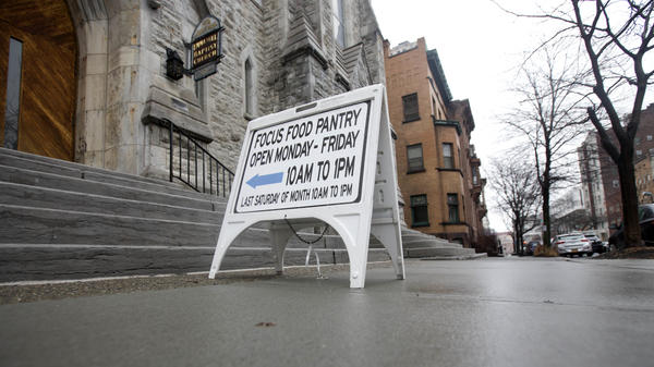 A sign sits on a sidewalk outside the Interfaith Food Pantry at Emmanuel Baptist Church in February in Albany, N.Y. Congress may be under more pressure than usual to cut safety net spending — health care, housing assistance, welfare and food aid — to help pay for Trump's tax cut plans.