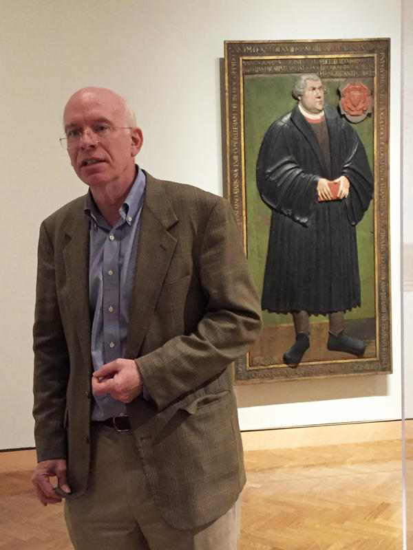 Minneapolis Institute of Art curator Tom Rassieur stands in a gallery showcasing objects honoring the 500th anniversary of Martin Luther posting his <em>95 Theses</em> against the Catholic Church.