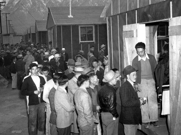 People wait in line for their housing assignment at the Manzanar internment camp in the California desert in 1942. More than 110,000 people of Japanese ancestry were removed from their homes and placed in camps in several states during World War II.