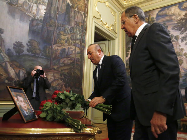 In Moscow, Russian Foreign Minister Sergey Lavrov (right) and Turkey's Foreign Minister Mevlut Cavusoglu offer flowers in memory of Andrei Karlov, Russia's ambassador to Turkey. Karlov was fatally shot Monday in Ankara.