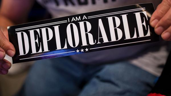 "A supporter of Republican presidential candidate Donald Trump shows a bumper sticker reading ""I am a Deplorable"" at Mohegan Sun Arena in Wilkes-Barre, Pa., on Oct. 10. The term references comments by Hillary Clinton that suggest some Trump supporters are ""deplorables."""