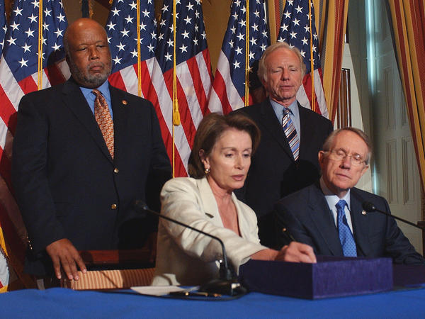 Then-House Speaker Nancy Pelosi of Calif., seated, left, signs homeland security legislation during a ceremony on Capitol Hill in Washington, in Aug. 2007. Pictured with Pelosi are Rep. Bennie Thompson, D-Miss., who sponsored the legislation standing left, then-Sen. Joseph Lieberman, I-Conn., standing, right, and then-Senate Majority Leader Harry Reid of Nev.