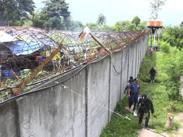 Police officers patrol outside the walls of the North Cotabato District Jail in the Philippines after a mass escape early Wednesday.