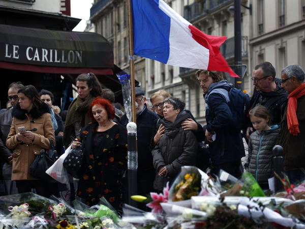 People gather outside Le Carillon, a bistro in Paris's 10th arrondissement that was attacked on Friday.