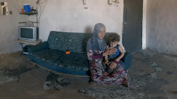 """A Syrian woman and her child sit in their refugee living space in Lebanon. They are featured in Four Walls, <a href=""""https://www.rescue.org/four-walls#four-walls-vr"""">a virtual reality presentation</a> by the International Rescue Committee."""