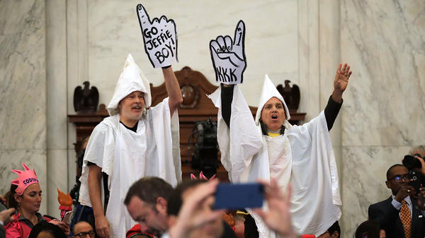 Protesters wearing white sheets shout at Sen. Jeff Sessions as he arrives at the Russell Senate Office Building on Monday for his confirmation hearing.