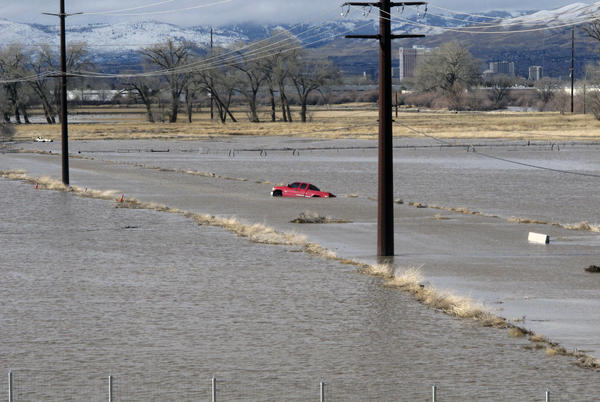 A red pickup truck sits abandoned on a closed road Monday at a University of Nevada, Reno, research farm bordering the Truckee River south of U.S. Interstate 80.
