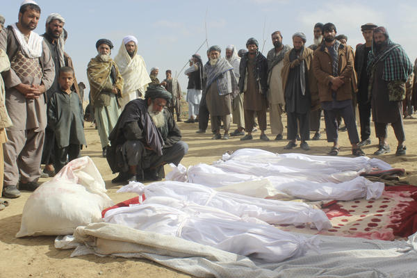 Afghan villagers gather around several victims' bodies who were killed in the November battle in Kunduz province, Afghanistan.