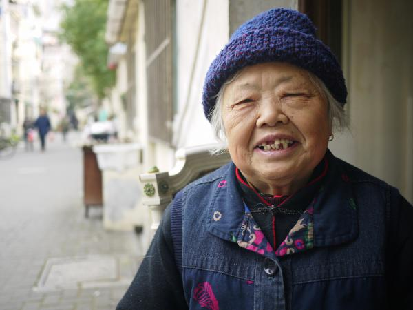 Ni Jindi, 94, sits at the entrance to Rising Peace Lane in central Shanghai. This is one of her favorite times of year, as millions of people leave the city to return to their hometowns, and Shanghai returns to its natives, like her.