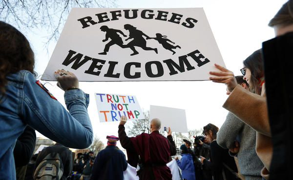 Protesters hold signs near the White House during a protest about President Trump's immigration policies on Wednesday. A proposed presidential action would freeze immigration from seven mostly Muslim countries for security reasons. But the list does not include any of the countries whose nationals have killed Americans in the U.S. since Sept. 11, 2001.