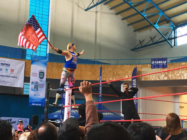Sam Polinsky, known by his <em>lucha libre</em> wrestling moniker Sam Adonis, enters the ring waving his Trump American flag and riling up the audience in Mexico City.