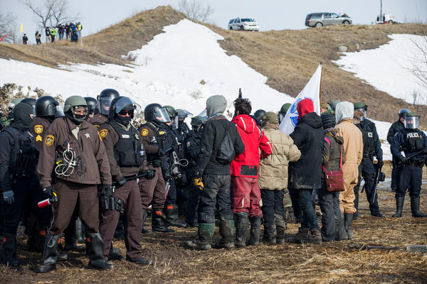 Protestors line up, arms linked, in peaceful protest as police enter the Oceti Sakowin camp on Thursday morning. All of the demonstrators were arrested.