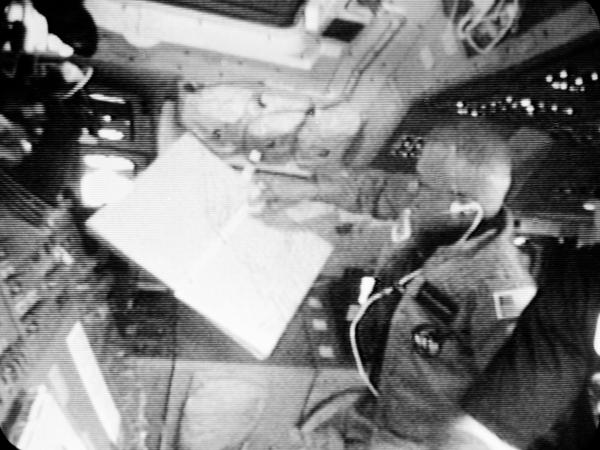 McCandless, mission specialist aboard the shuttle Challenger in February 1984, looks at a map showing the path of the spaceship.