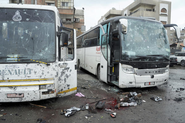 This photo, released by the Syrian official news agency SANA, shows bloodied streets and damaged buses after a bombing in Damascus on Saturday.
