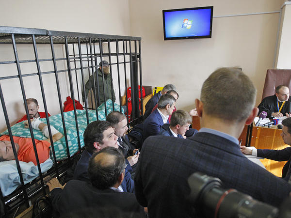 Roman Nasirov (left, in orange), the suspended head of Ukraine's tax service, lies inside the defendant's cage during his court hearing in Kiev on March 5. He was first detained in a hospital, claiming illness. Nasirov is accused in an embezzlement scheme amounting to more than $70 million.